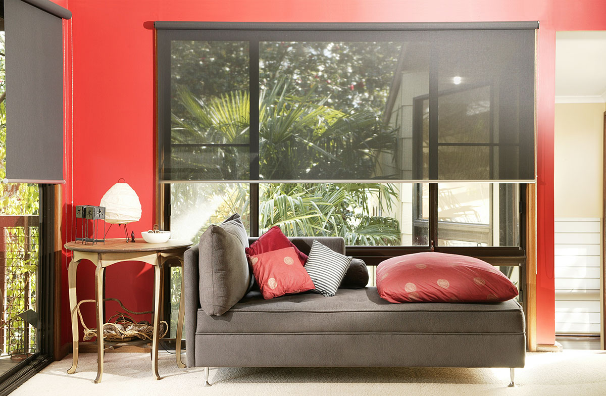 brown couch with red pillows and red walls with interior shades halfway down
