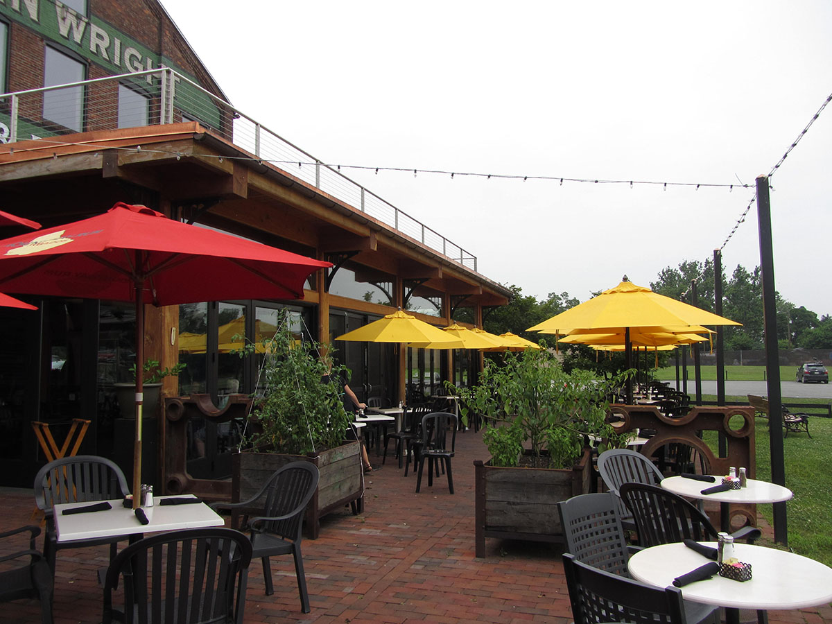 yellow and red umbrellas with lights reaching across above a brick patio with tables