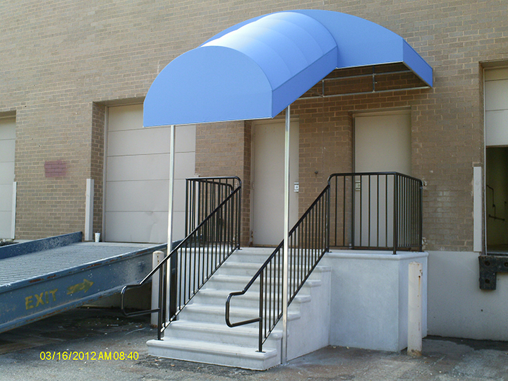 light blue canopy that extends out over the stairs to the building entrance