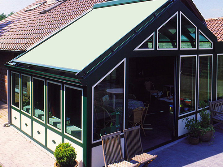 green conservatory awning over top a sun room of a restuaurant