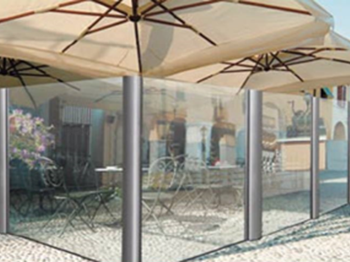 two umbrellas over tables next to glass dividers that are glass from top to bottom