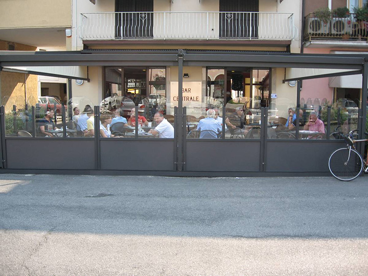 view of people eating at a restaurant with a perogla open and glass dividers