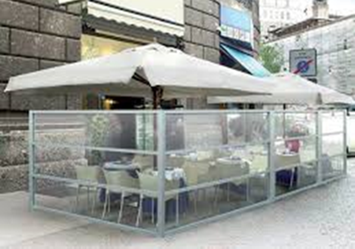 glass wall dividers around an outdoor seating area at a cafe