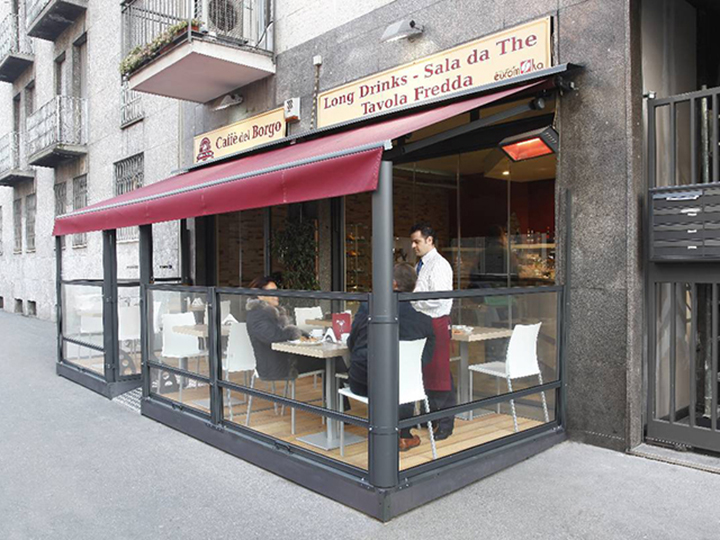 small cafe with red awning and glass dividers for outdoor seating