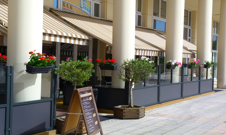 tan and white pin striped awning with restaurant sign in front and flowers