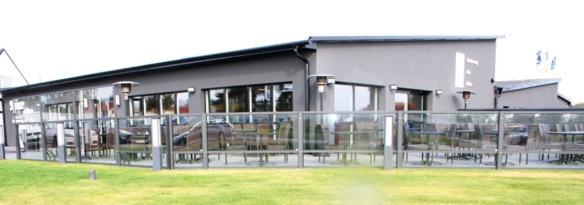 large gray building with glass dividers next to grass area