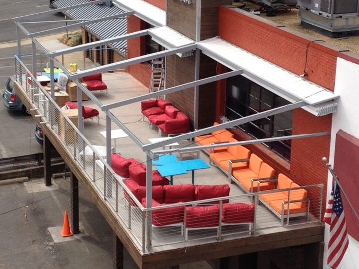 pergola over dining outdoor area with red and orange sofas and a blue table