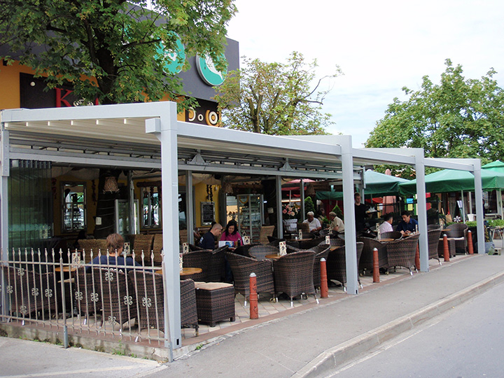 white pergola with people sitting down at bar and restaurant under it