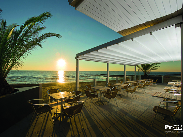 pergola over an oceanfront seating area with palm trees sand and a sunset