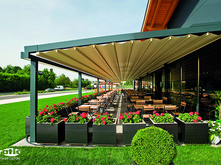 cream retractable awning that is opened entirely over a long dining area outside