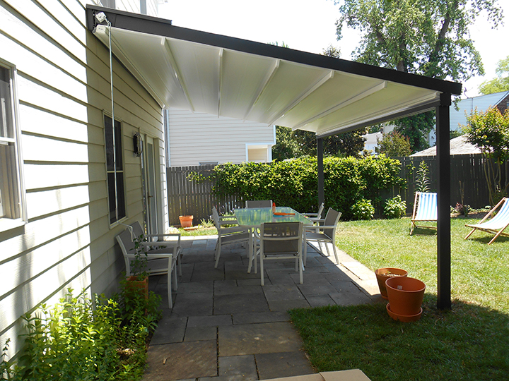White Pergola Awning On A White House Extending Over Backyard Patio