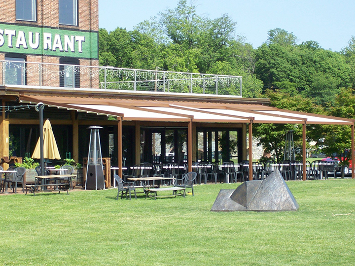 green restaurant sign with pergola extended over outdoor seating area