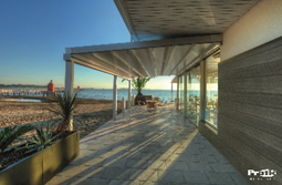 pergola over patio that is oceanfront and next to a sandy area