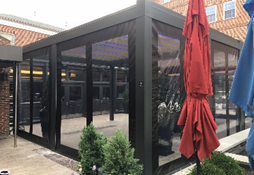 red and blue umbrella closed next to a black pergola with screens