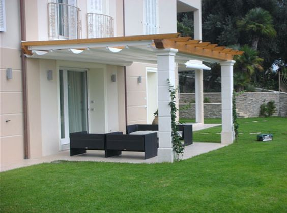 pink house with wooden pergola and white columns