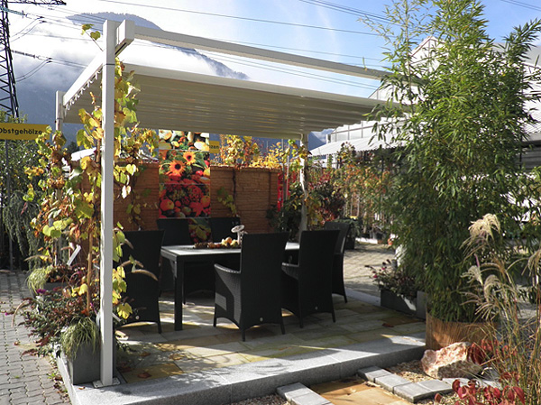 awning surrounded by overflowing garden and a seating area centered under