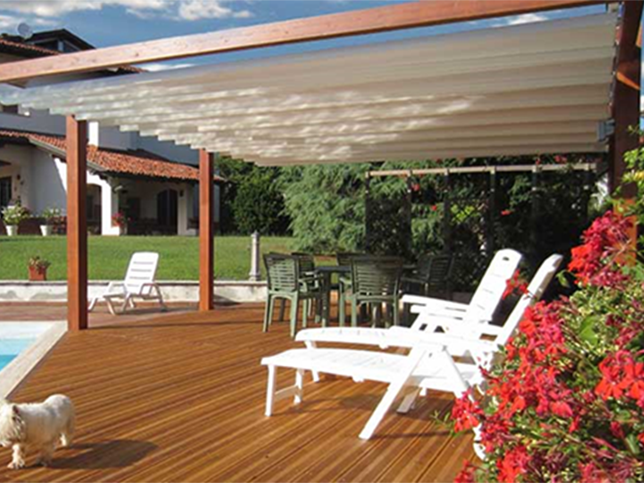pergola covering a large pool patio with white lounge chairs and red flowers