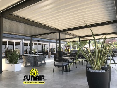 White pegola awning over sitting area furniture
