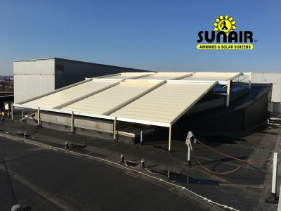 A white pegola awning canopy over a commercial area