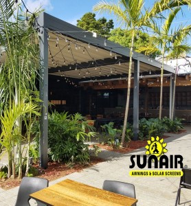 A wooden awning over restaurant garden and furniture