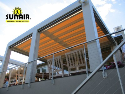 A metal pergola awning over furniture on a patio
