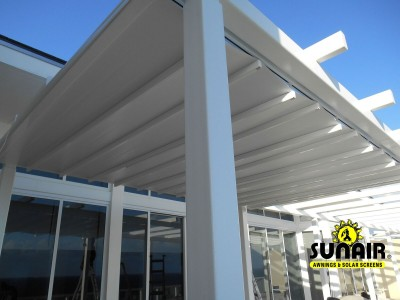 A white metal pergola awning in front of windows
