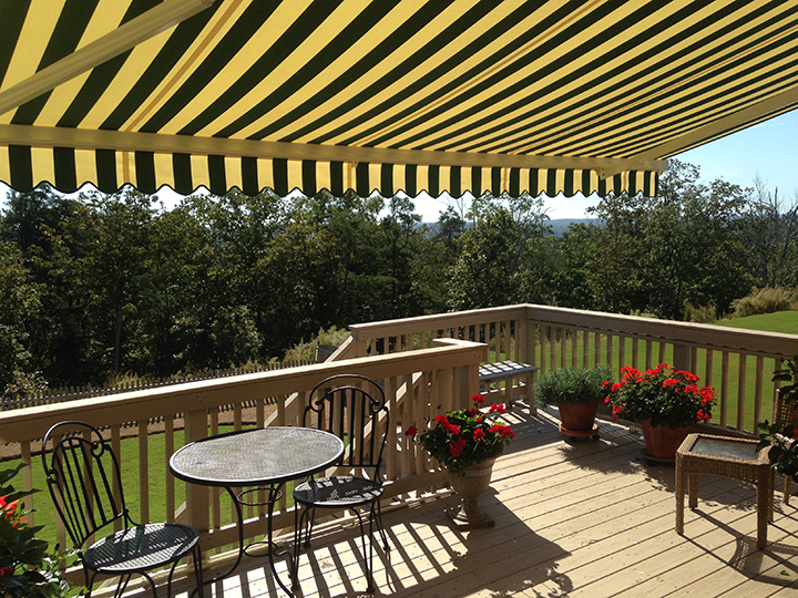 black and yellow striped awning open over a deck