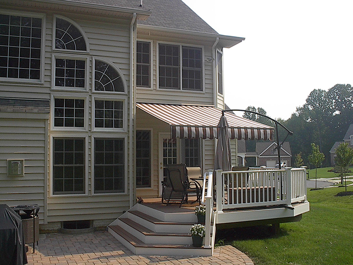 House With Many Windows And Small Deck That Has A Close Umbrella And An  Open Awning ...