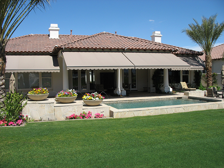 three tan colored awnings over a small pool area