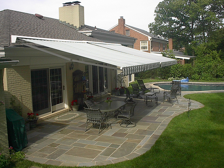 two retractable awnings side by side over a stone patio with a pool on the right