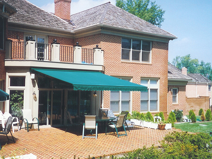 bright blue awning on a brick house with a brick patio