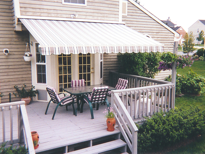Striped awning over double doors with outdoor chairs and table on a deck