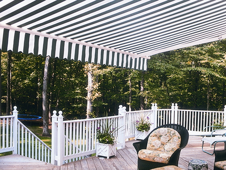 navy blue and white striped large awning extended over large deck with trampoline in the back