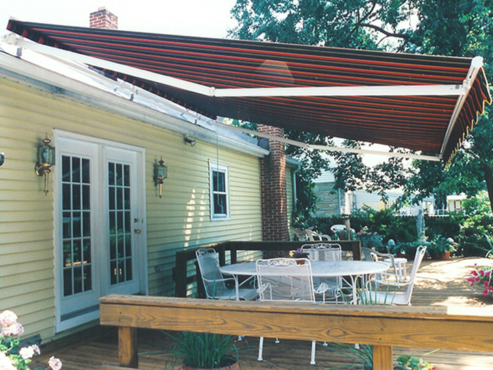 red striped awning that extends over patio of a yellow house
