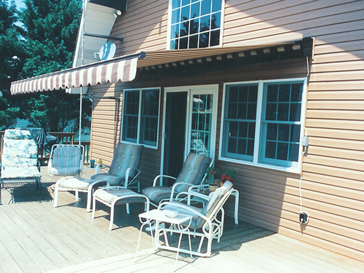 striped awning extended over deck furniture