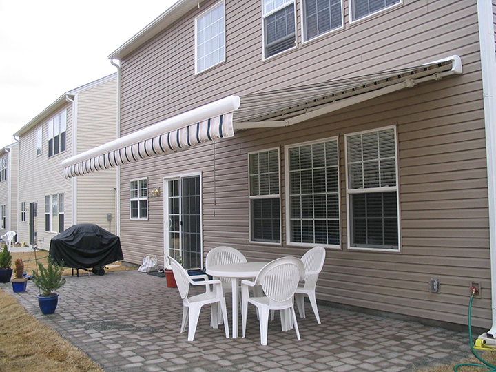 a tan house with shade open and white dining set under with a grill covered to