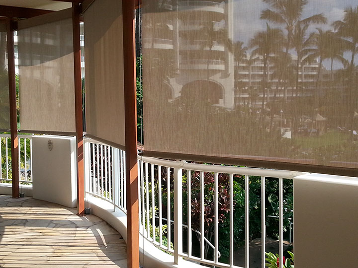 screen shades pulled down over railing overlooking palm trees and resort