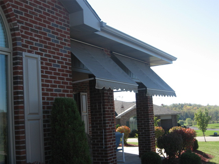 brick house with small gray awnings and a design on the end