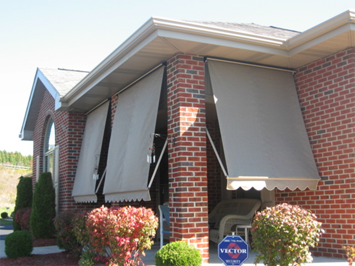three gray awnings that cover small front porch of a brick house