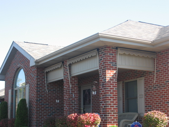 brick house with three gray awnings retracted all the way to show front porch and front door