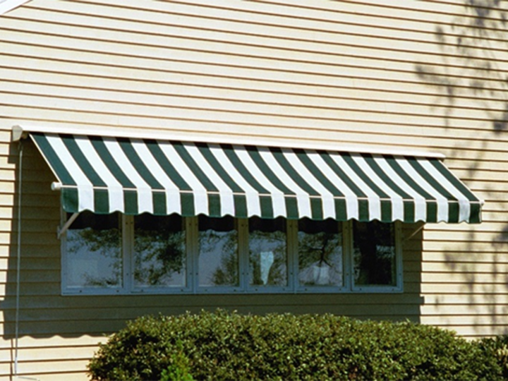 close up of siding with green and white striped awning over a narrow set of windows