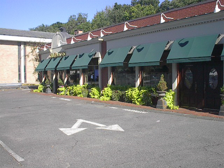 7 green awnings over windows and doors of a storefront