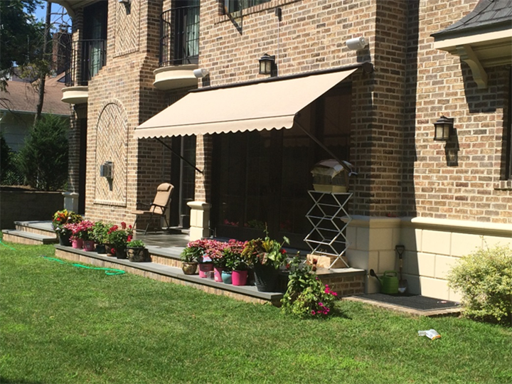 Cream colored awning over entrance with small garden on steps