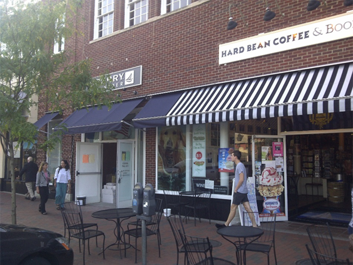 Hard Bean Coffee storefront with striped awning over the entrance and window