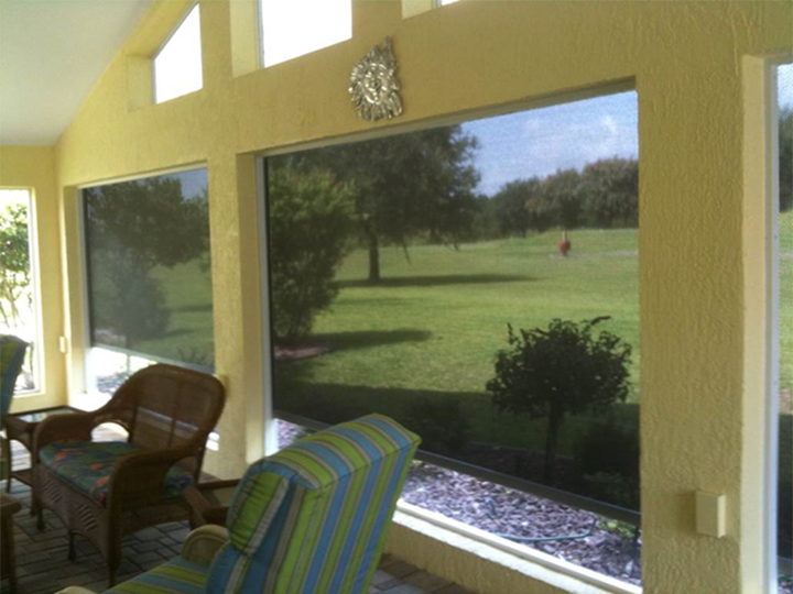 inside a yellow sunroom looking out at the yard through large screens