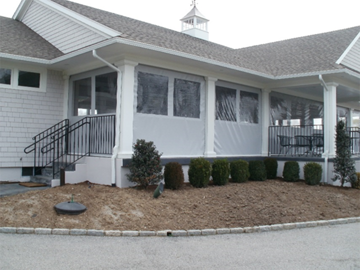 white home with small bushes around front and a screened in porch